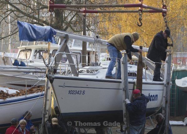 Die Gurte des Krans werden um das Segelboot geschlagen.