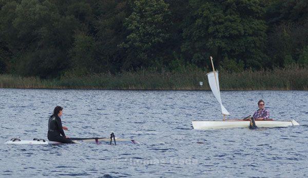 Ein Kanu unter Segel nähert sich der treibenden Windsurferin