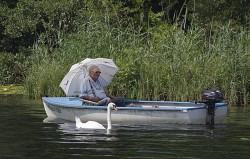 Mann mit Sonnenschirm im Boot
