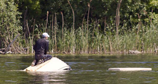 Sinkendes Boot mit nassem Mann