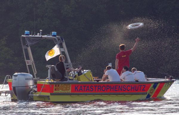 ASB Reetungsboot. Ein Retter wirft den Rettungsring über Bord.